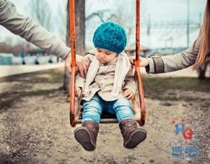 Kind op schommel met twijfel tussen ouders
